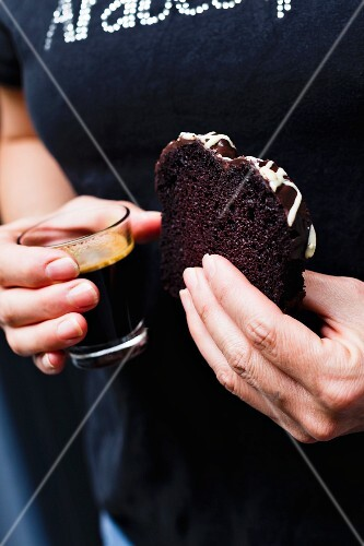 A woman holding a glass of coffee and a slice of chocolate sponge cake with chocolate glaze