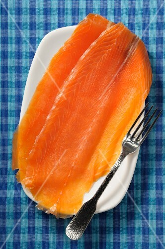 Two slices of smoked salmon on a plate (seen above)