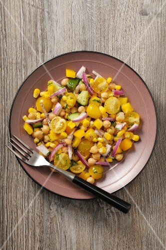 A yellow vegetable salad with tomatoes, sweetcorn, peppers and chickpeas