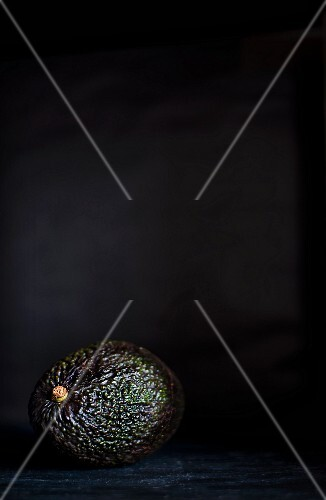 An avocado on a slate platter against a black background