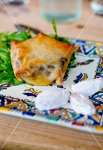 Pastilla filled with dark and pine nuts on an Arabic plate with goat's cheese and salad (Morocco)