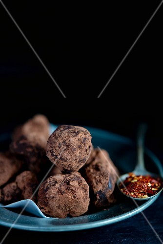 Homemade chocolate chilli truffles and a spoonful of dried chilli flakes
