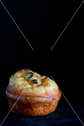A Yorkshire pudding on a slate platter against a black background