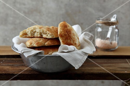 A stack of pita bread in a metal bowl