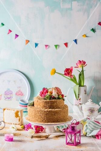 Russian honey cake decorated with flowers beneath colourful bunting