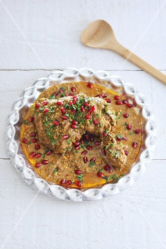 Chicken leg in a pistachio nut sauce with pomegranate seeds