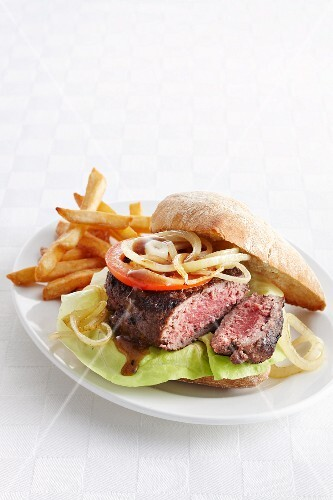 A steak burger with chips