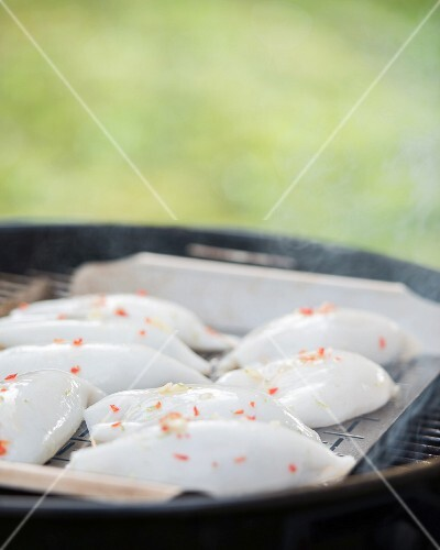 Squid filled with prawns and rice on a barbecue