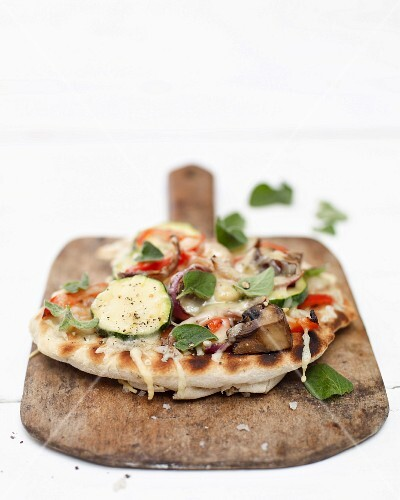 A mini vegetable pizza on a wooden board
