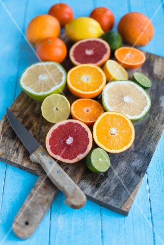 Various halved citrus fruits on a chopping board with a knife