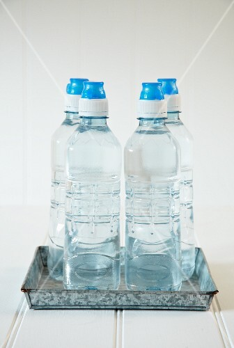 Four bottles of water on a metal tray