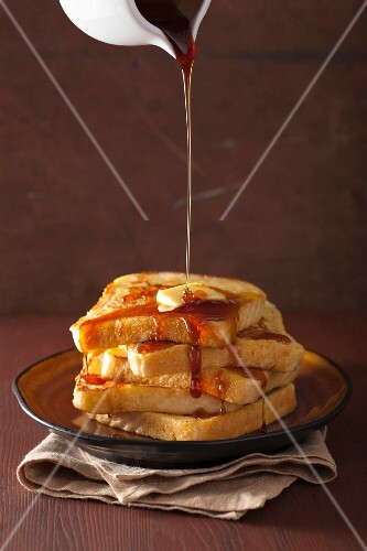 Caramel sauce being poured over French toast