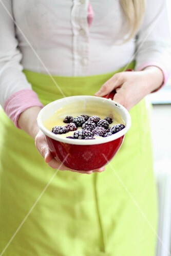 A woman holding a bowl of pudding and blackberries