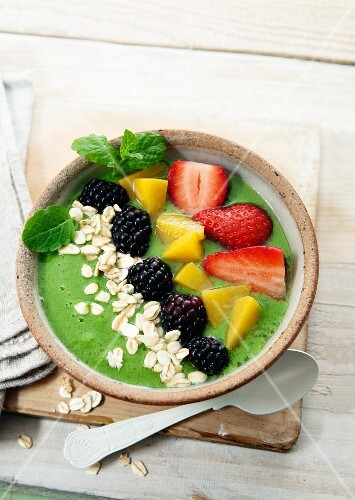 A smoothie bowl made with cabbage, apple and kiwi garnished with strawberries, peaches, blueberries and oats