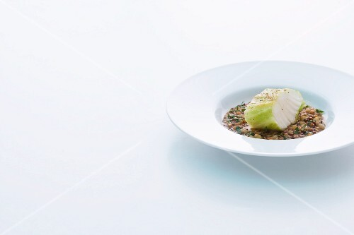 Cod wrapped in point of cabbage on a bed of lentils
