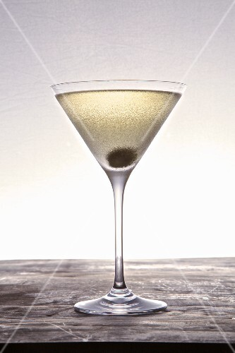 A martini with a caper berry