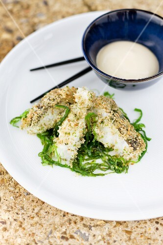 Grilled slices of fish with sesame seed coating on a seaweed medley with a tofu dip