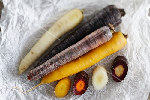 Various different coloured carrots on a piece of white parchment paper