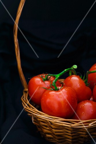 Fresh tomatoes in a basket against a black background