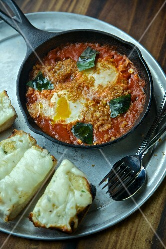 Eggs with tomatoes and basil in a pan served with cheese on toast