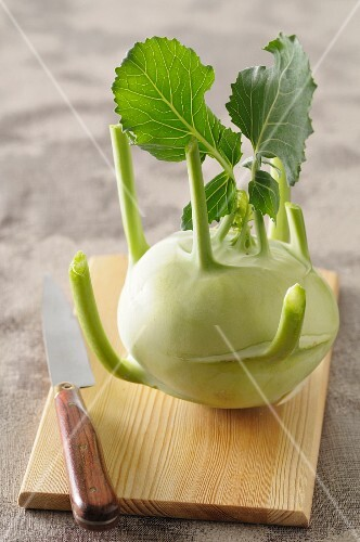A kohlrabi with leaves on a wooden board