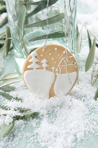 About biscuits iced with a winter landscape between olive sprigs on a table covered with snow