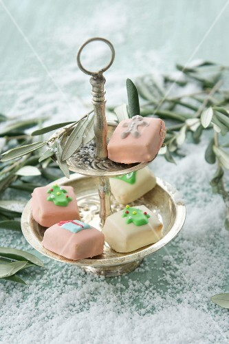 Christmas petit fours decorated with marzipan between olive sprigs on the table covered with snow
