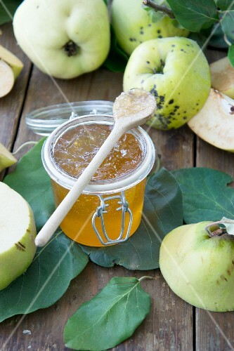 Quince jam in a glass jar and fresh quinces