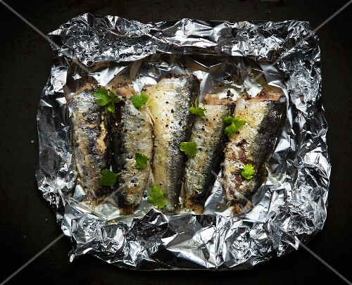 Sardines with coriander in aluminium foil for grilling (seen from above)