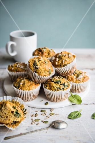 A stack of savoury spinach and carrot muffins on a white board