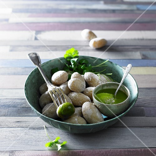 Potatoes baked in salt with a green sauce