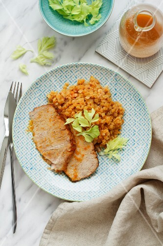 Slices of roast pork with red lentils (seen from above)
