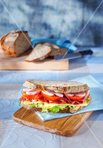 A sandwich on a light blue napkin on a wooden board with a sliced loaf of bread in the background