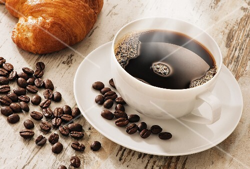 A steaming cup of coffee with coffee beans and a croissant on a light wooden surface