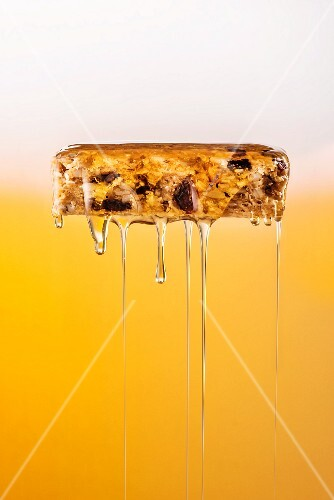 Honey being poured over a muesli bar