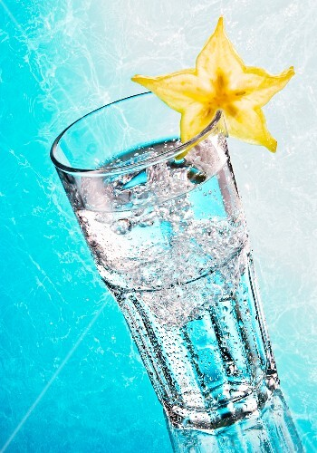 A glass of water garnished with a slice of star fruit on a light blue surface