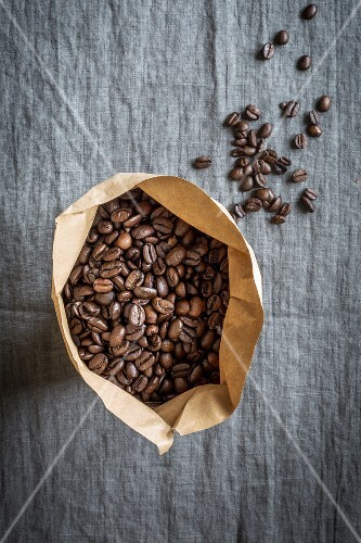 Coffee beans in a paper bag on a grey linen cloth