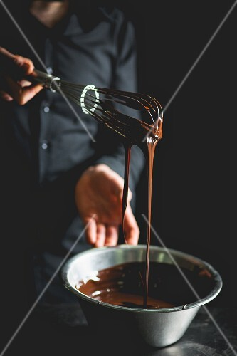 Liquid chocolate dripping from a whisk into a stainless steel bowl