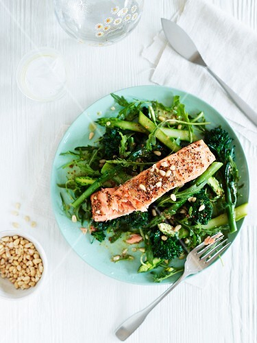 A salmon fillet on a bed of green vegetables with pine nuts