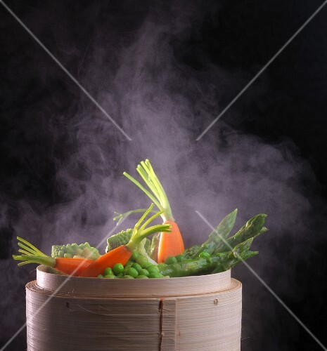 Vegetables being steamed in a bamboo basket