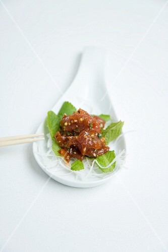 Tuna fish sashimi in an orange and mustard sauce with fresh mint