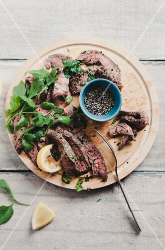 Strips of grilled pepper steak with rocket and parsley