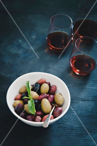 A bowl of mixed olives with glasses of red wine