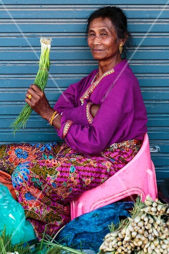 A smiling market woman selling spring onions in Vientiane, Laos