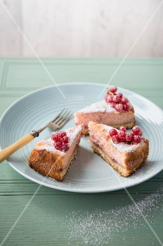 A three slices of sugared redcurrant cheesecake on a plate.