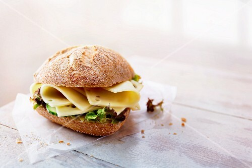 A rye bread roll with cheese and lettuce