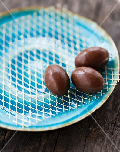 Three small chocolate eggs on a blue plate