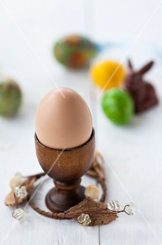 A close up of an egg in an egg cup with colourful eggs and an Easter bunny in the background