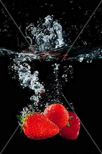 Strawberries falling in water with a splash