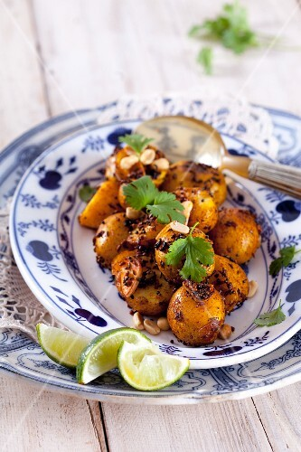 Fried potatoes with fenugreek, caraway, coriander, peanuts, black mustard seeds and limes